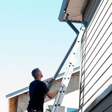 Man Installing downspout on ladder
